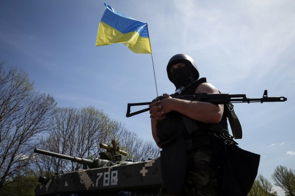 A Ukrainian soldier stands guard near an APC at a checkpoint outside the city of Slaviansk